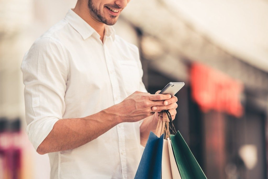 man in white shirt holding shopping bags while texting