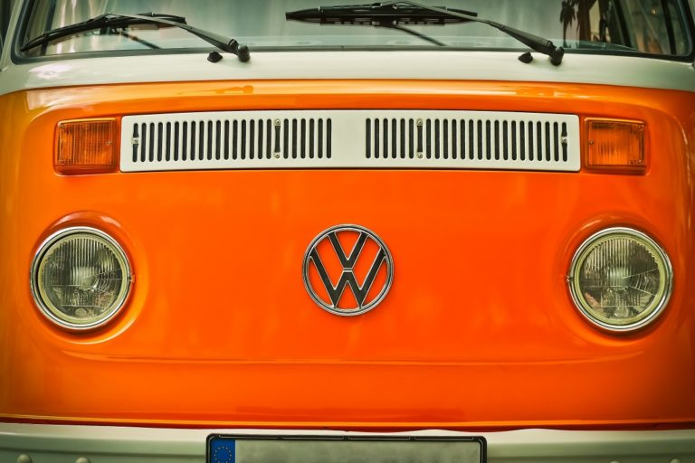 close up shot of volkswagen logo in an orange car