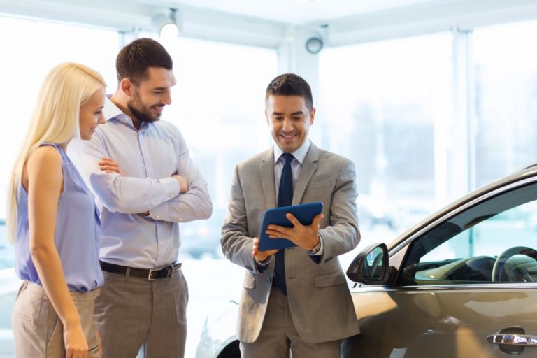 couple looking for car being accommodate by a car salesman