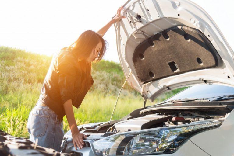 Woman attempting to repair broken down car