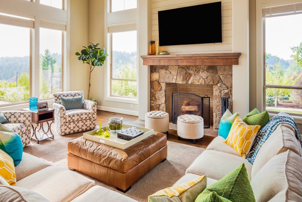 Beautiful Furnished Living Room Interior in New Luxury Home with Fireplace, Couches, Chairs, and Television