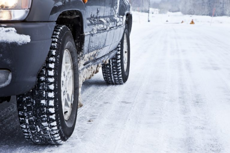 Close up of a cars tires on a snowy road