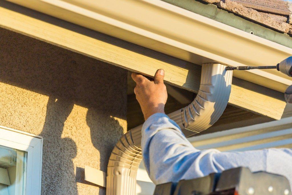 man repairing a gutter