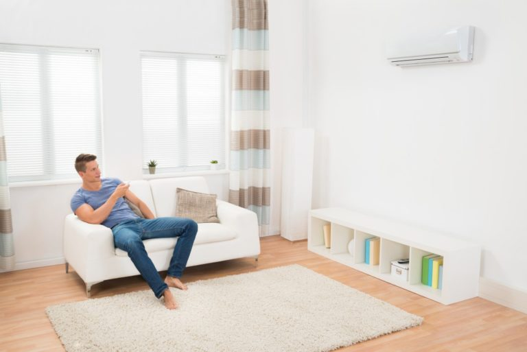 man sitting in his living room using the airconditioner