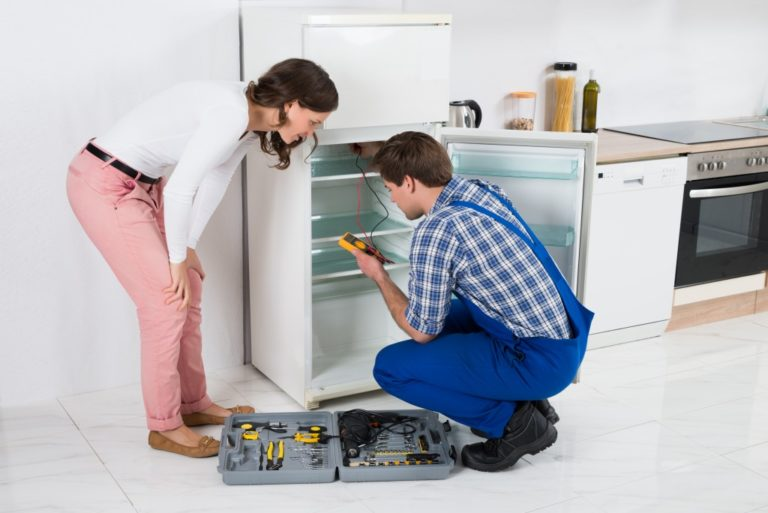 Worker Repairing Refrigerator In Kitchen Room