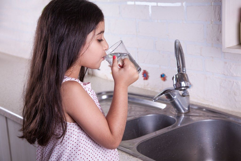 child drinking water from the sink