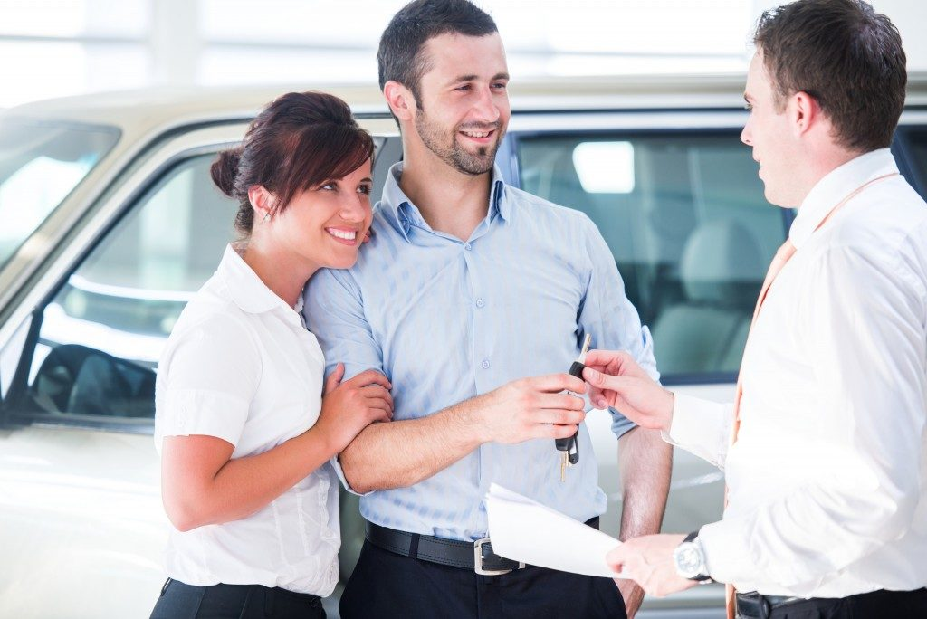 smiling couple talking to a car dealer