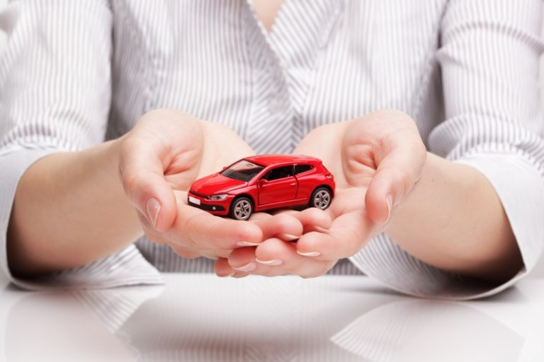 car in woman's hand, selling or buying a car concept