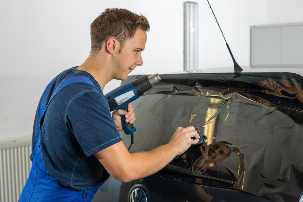 Worker in garage tinting a car window with tinted foil or film