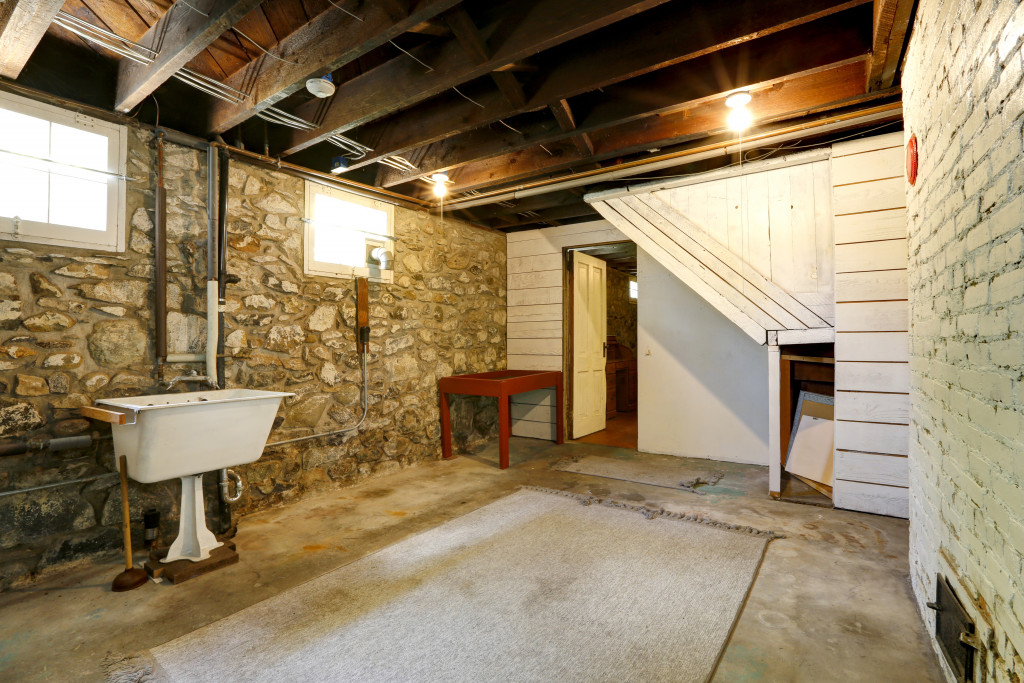 Basement empty room interior with stone wall trim and brick wall with fireplace